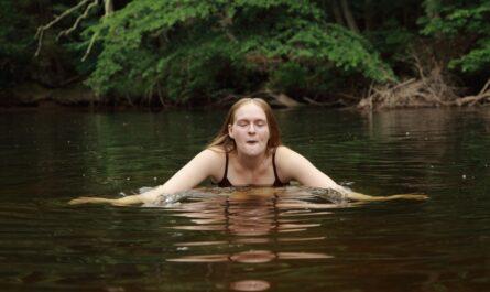 Dívka provádí ve studeném rybníce otužování.