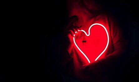 Svítící srdce, které svírá dívka.
