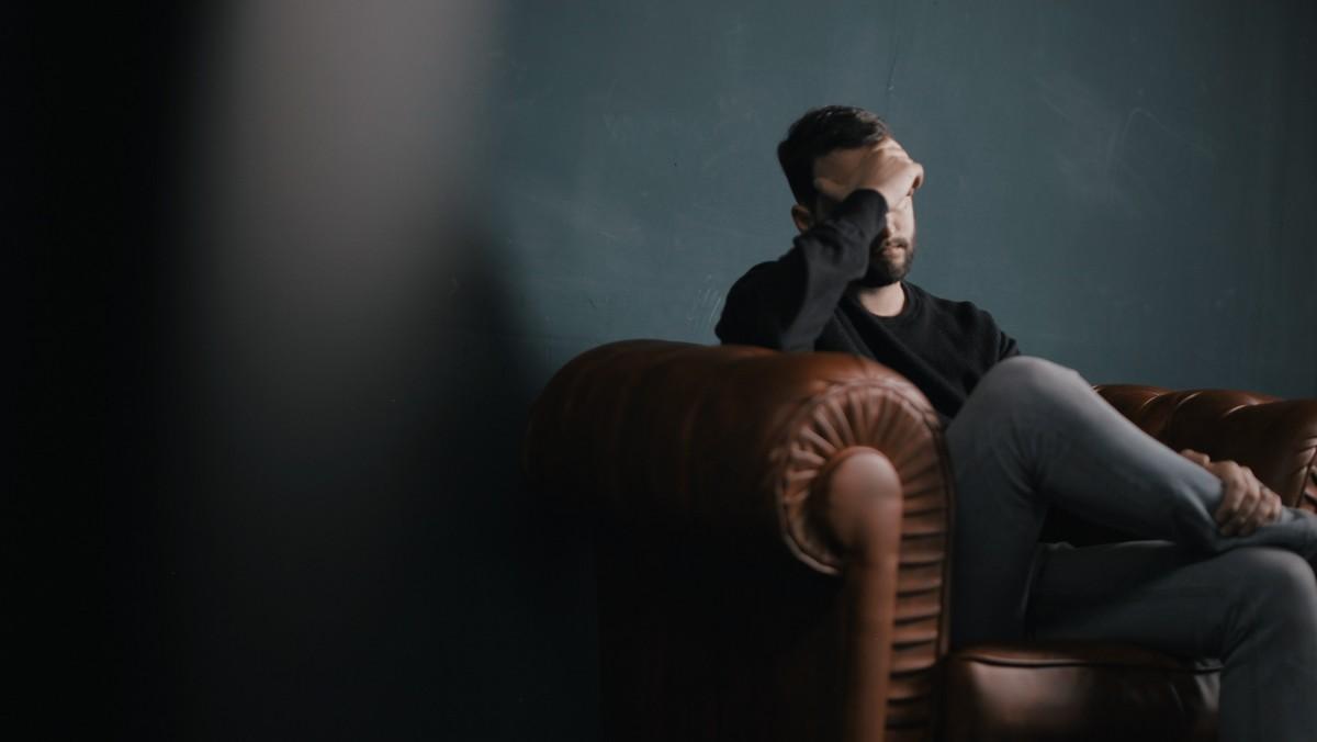 Muž sedící na pohovce, kterého sužuje stres.